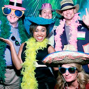 Photo booth image of corporate event employees wearing props in front of a tropical backdrop